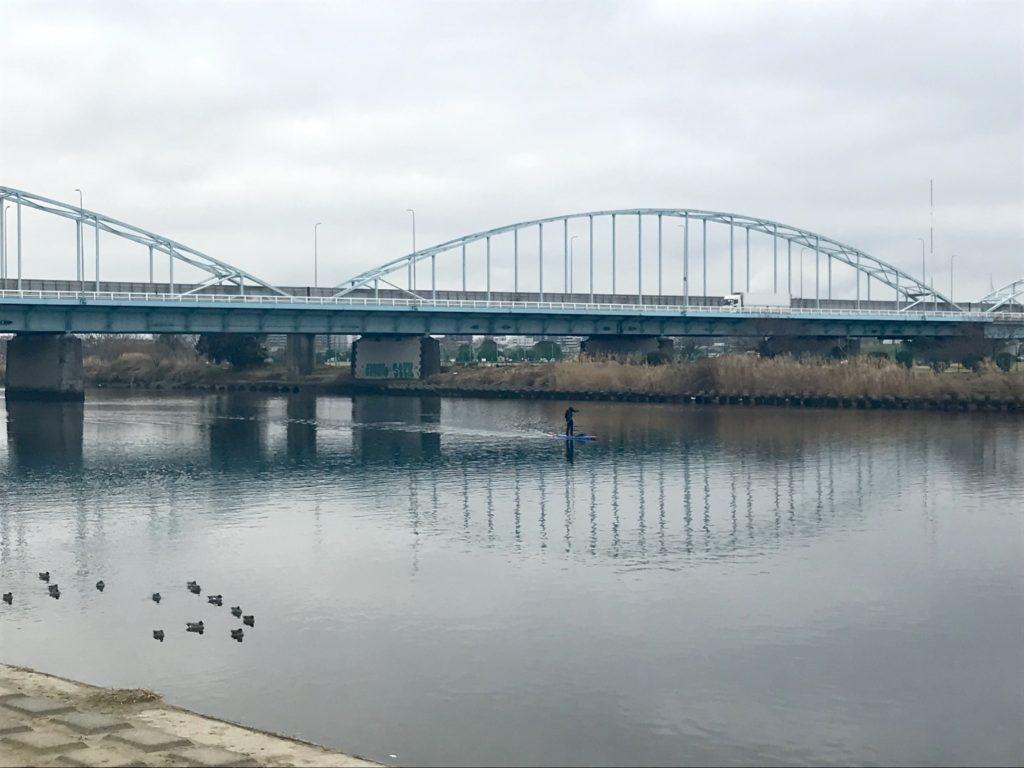 多摩川でSUPを漕ぐ人