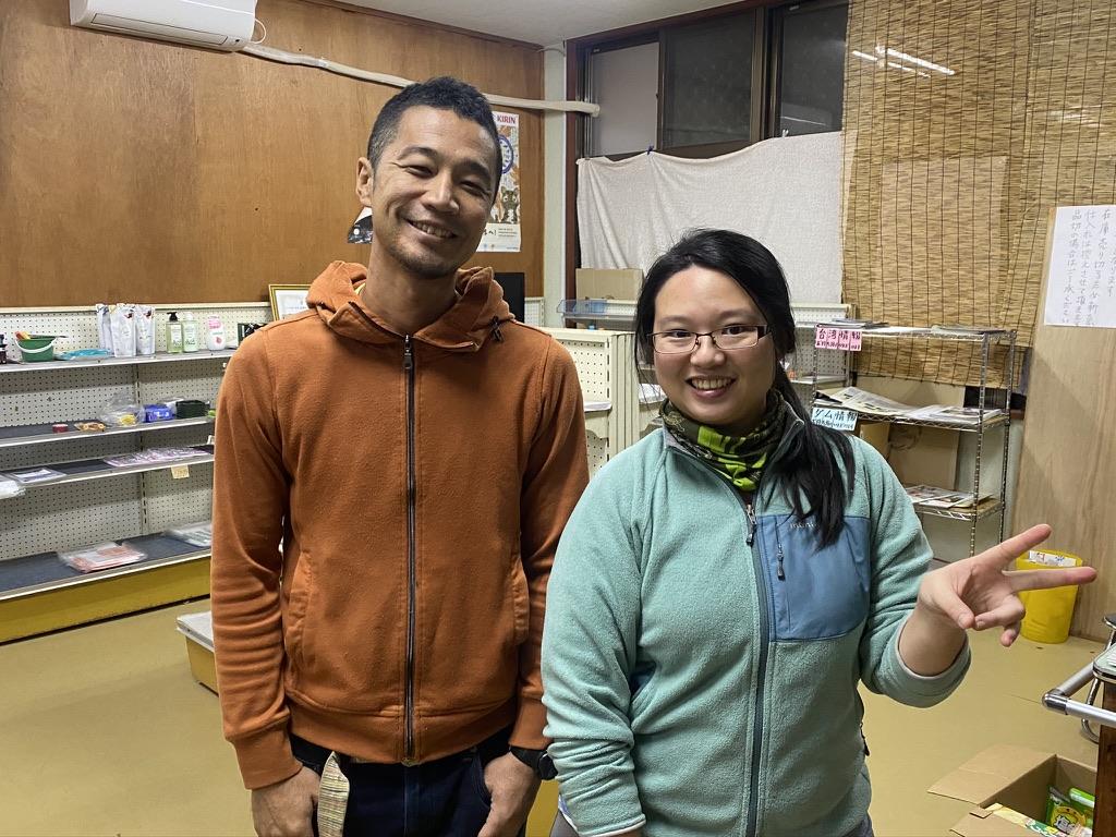 辺野喜共同売店の前の店長チョーさんと移住者のアサハラさん。